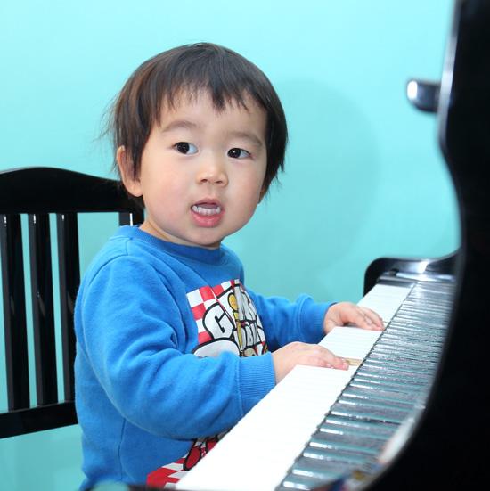ピアノの鍵盤の前に座りこちらを向く幼児の男の子の写真