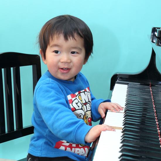 ピアノを弾く幼い男の子の写真