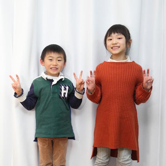 ピースをする小学生の姉弟の写真