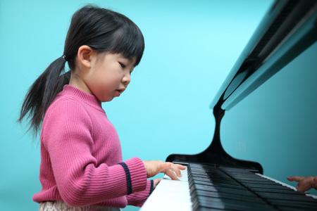 ピアノを弾く幼い女の子の写真