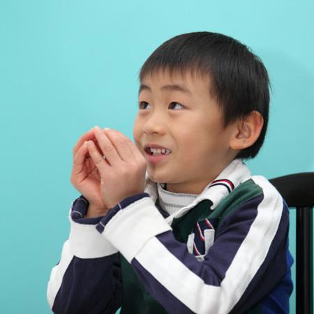 手をお椀にして合わせる小学生の男の子の写真