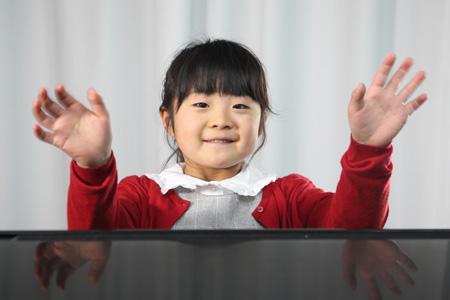 ピアノの向こうからこちらに向かって笑顔で手を振る小学生の女の子の写真