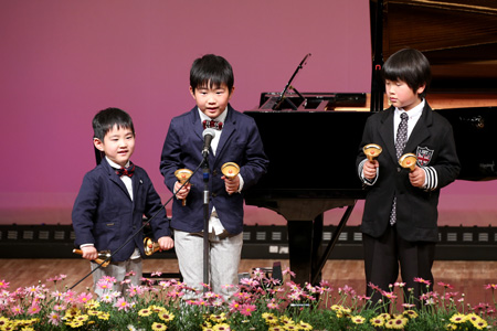 発表会の舞台でミュージックベルを演奏する3人の男の子の写真
