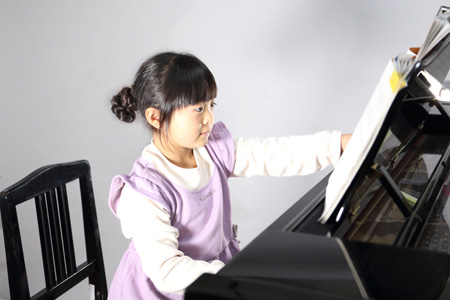 ピアノを弾く小学生の女の子の写真