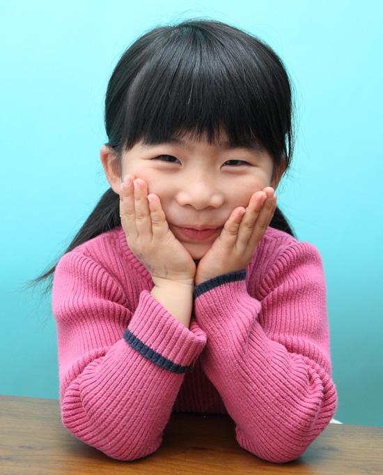 両手を頬に当ててこちらに微笑む女の子の写真
